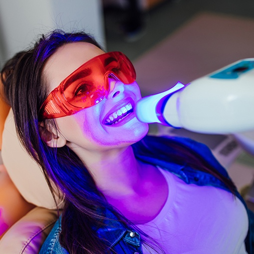 Woman receiving in office teeth whitening treatment
