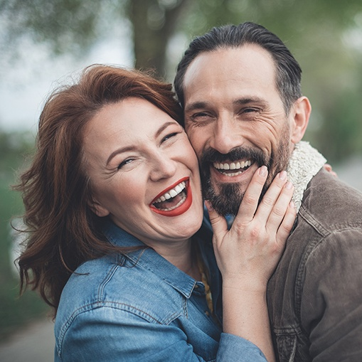 Man and woman smiling together after metal free dental crown restoration