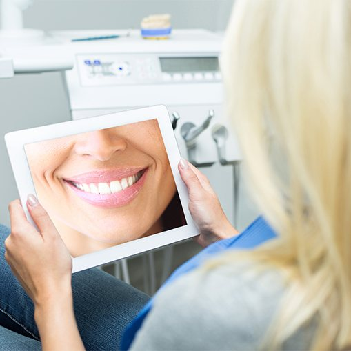 Womanlooking at virtual smile design on tablet computer
