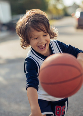 Little boy with healthy smile playing basketball after children's dentistry visit