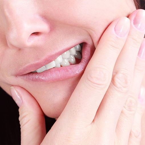 Patient in need of root canal therapy holding jaw in pain