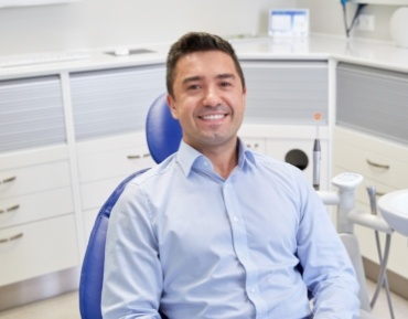 Smiling man in dental office for preventive dentistry