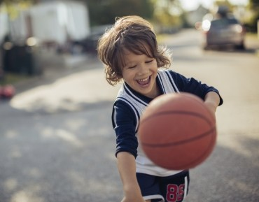 Little boy with healthy smiling playing basketball after children's denistry visit