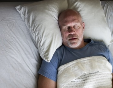 Man sleeping soundly thanks to sleep apnea therapy